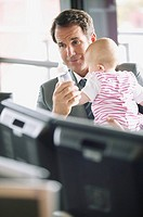 Businessman feeding baby