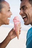 Multi-ethnic couple eating ice cream cone