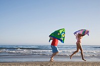 Multi-ethnic couple running with beach towels