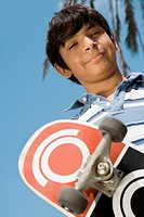 Hispanic boy holding skateboard