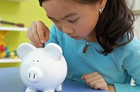 Young girl placing coin in coin bank