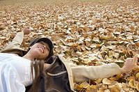 Girl lying on fallen leaves