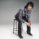 Young man sitting on a stool (thumbnail)