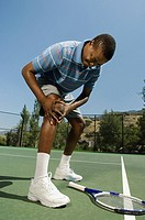 Tennis player holding injured knee
