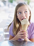 Young girl on outdoor patio licking ice cream cone