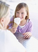 Young girl and woman on outdoor patio with ice cream cone
