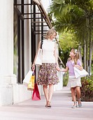 Woman and young girl outdoors with shopping bags