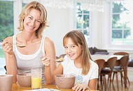 Woman and young girl in kitchen eating breakfast