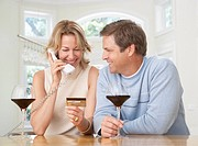 Couple in kitchen with credit card on telephone