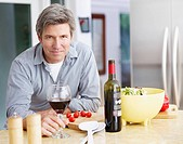 Man in kitchen preparing meal and drinking wine