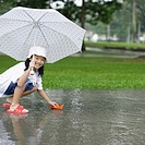 Young girl outdoors in rain playing with paper boat (thumbnail)