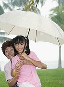 Woman and young girl outdoors in park by lake with umbrella