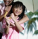 Woman and young girl outdoors in rain with umbrella laughing