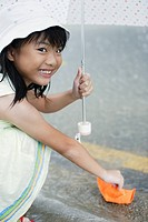 Young girl outdoors in rain with umbrella playing with paper boat