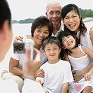 Man taking picture with digital camera of family outdoors on beach