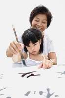 Woman and young girl indoors painting Chinese letters