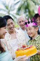 Young boy outdoors celebrating birthday with family