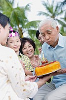 Man outdoors celebrating birthday with family