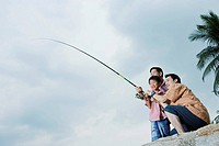 Two men helping young boy outdoors fishing