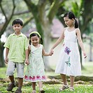 Three young kids outdoors at park holding hands