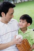Man and young boy outdoors at park with baseball and glove