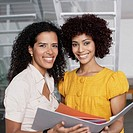 Two businesswomen in office space holding folder