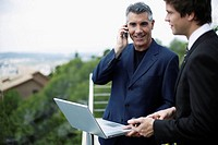 Two businessmen outdoors on balcony with laptop and mobile phone