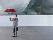 Businessman standing outdoors on top of building with umbrella