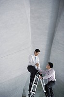 Two businessmen on ladder in structure holding hands