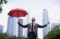 Businessman outdoors holding umbrella with arms out
