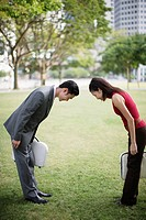 Two businesspeople outdoors in park bowing