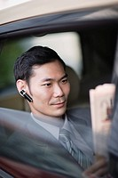 Businessman wearing earpiece in car with newspaper