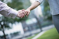 Two businesspeople outdoors holding hands