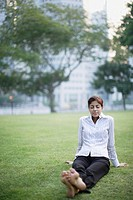 Businesswoman outdoors sitting in park relaxing