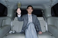 Businessman with champagne flute in limousine