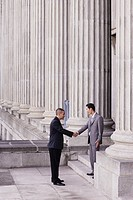 Two businessmen outdoors on steps shaking hands