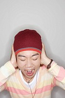 Man indoors screaming and covering ears (thumbnail)