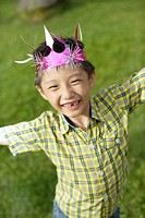 Young boy outdoors wearing party hat (thumbnail)