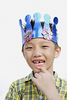 Young boy indoors wearing party hat and showing missing tooth