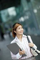 Businesswoman outdoors holding binder