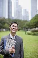 Businessman outdoors in park with newspaper