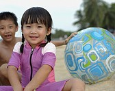 Two young kids outdoors at beach playing with ball