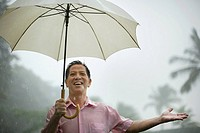 Man outdoors in rain with umbrella