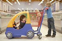 Young boy and young girl in grocery store with shopping cart