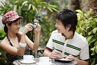 Couple on outdoor patio taking a picture with digital camera