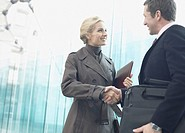 Two businesspeople outdoors shaking hands