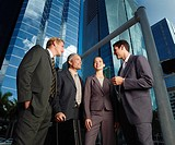 Four businesspeople outdoors by buildings talking