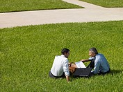 Two businessmen outdoors sitting in grass with paperwork