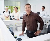 Four businesspeople in an office looking at camera