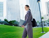 Businesswoman carrying paperwork on path outdoors